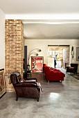 Wohnbereich mit Ledersessel und roter Couch, Blick in offene Küche
