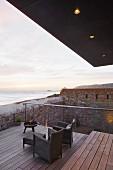 Blick von der Terrasse mit Sesseln auf Meer und Sonnenuntergang