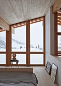 Bedroom in modern wooden house with view of wintry landscape