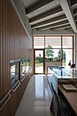 Designerküche mit Einbaugeräten und Mittelblock, im Hintergrund Terrassenzugang