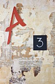 Letters and number on wall with layers of peeling paint