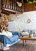 Lounge area on terrace with firewood stacked against wall