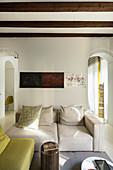 Beige two-seater sofa between two open doorways