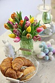 Croissants, Easter bunny and vase of tulips on wooden table