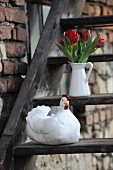 Hand-made fabric hen and white jug of red tulips on rustic wooden steps