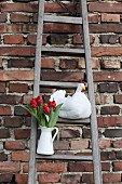 Hand-made fabric hen and white jug of red tulips on rustic wooden ladder