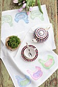Hand-made table runner with pattern of hens, potted plan and tea set