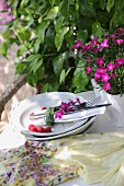 Blades of grass and scented pinks wrapped around napkin and cutlery on plate