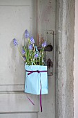 Paper bag of grape hyacinths and rosemary hung from door
