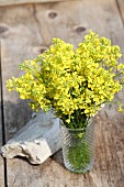Bunch of rapeseed flowers in glass vase with structured surface on weathered wooden boards