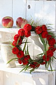 Wreath of red zinnias and switchgrass hung from shelf