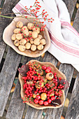 Wooden dishes holding red berries and medlars and walnuts