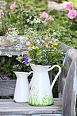 Wild flowers in painted jug on vintage garden bench