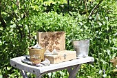 Kitchen herbs in wooden crate with pokerwork motif on garden table
