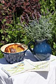 Hand-made pot holders, cake in ceramic pot and lavender in ceramic jug on white tablecloth on small garden table