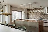 Edle, offene Küche mit Kücheninsel, Marmor-Küchenarbeitsplatte und geometrischem Wandfliesenmuster