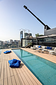 Long, narrow swimming pool and sofa combination on roof terrace with view of city