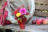 Strauß aus Dahlien und Hagebutte mit roten Weinblättern umwickelt
