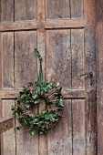 Wreath of willow and green ivy tendrils hung on rustic wooden door