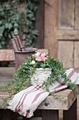 Blumengesteck mit rosafarbenen Rosenblüten und Efeuranken auf rustikalem Holztisch
