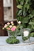 Romantic arrangement of ivy wreaths, roses and lit candle in glass vases