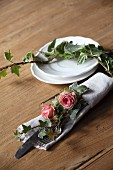 Romantic arrangement of roses and ivy on linen napkin with cutlery and place setting