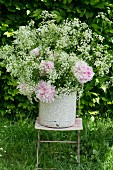 Enamel bucket of chervil and peonies on garden chair