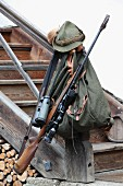Backpack and hunting equipment on newel post of wooden staircase outside house