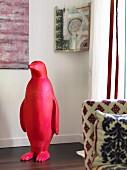 Red plastic penguin in front of modern artwork in corner of room