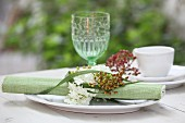 Rolled place mat with napkin ring made from flowers