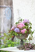 Luxuriant bouquet of hydrangeas and tendrils of berries in urn