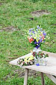 Arrangement of cottage-garden flowers on table on lawn