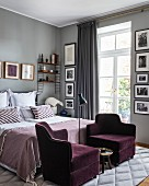 Two purple velvet armchairs at foot of bed in glamorous bedroom