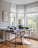 Designer furniture in workspace in window bay with herringbone parquet floor