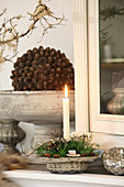 Rustic wreath and lit candle in small basket