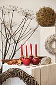 Vier rote Kerzen in Äpfeln auf einem weißen Holzblock