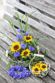 Sunflowers, cornflowers, blades of grass and clematis tendrils in wire basket next to wreath of cornflowers on wooden bench
