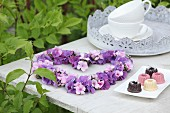 Heart-shaped wreath of hydrangea and phlox flowers on garden table