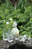 Verschiedene weiße Blumen in Glasväschen auf einem Steintrog