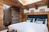 Double bed with rustic headboard in attic bedroom with ensuite bathroom