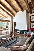 Rustikales Wohnzimmer mit Holzbalkendecke und Kamin