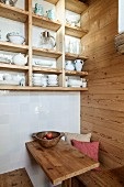 Crockery on open-fronted shelves on white-tiled wall above wooden benches and wooden table in seating area