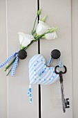 Pale blue, ornate, heart-shaped pendant and key next to white artificial flowers on cabinet door knobs