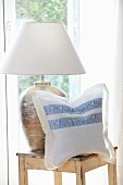 Cushion cover hand made from white linen and floral trim next to table lamp on wooden stool