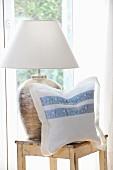 DIY-Kissenbezug aus weißem Leinenstoff und Blumenborte auf Holzhocker neben Tischleuchte