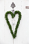 Candle lantern in heart-shaped box wreath hung on white wooden door