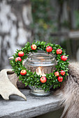Small wreath of box and red crab apples around candle lantern