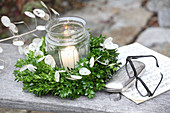 Glasses and case next to candle lantern in wreath of box and honesty