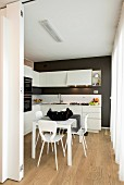Dining table and wooden floor in black and white kitchen