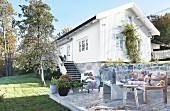 Gemütlicher Terrassenplatz in sommerlichem Garten vor weißem Holzhaus